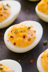 Very close-up overhead view of spicy deviled eggs on a dark background.