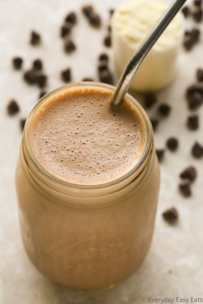 Overhead view of a Chocolate Protein Shake in a glass jar with a metal straw on a neutral background.