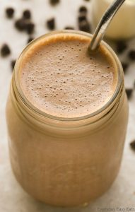 Close-up overhead view of a Chocolate Protein Shake in a glass jar with a metal straw on a neutral background.