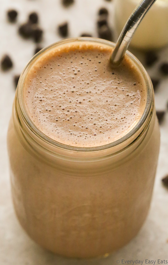 The Best Organic Food & Grocery Delivery Services: Close-up overhead view of a Chocolate Protein Shake in a glass jar with a metal straw on a neutral background.
