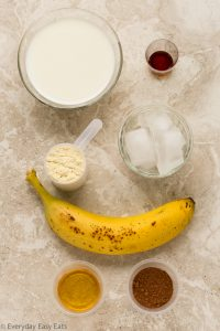 Overhead view of ingredients required to make Chocolate Protein Shake on a neutral background.