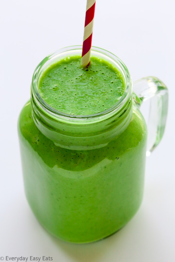 Overhead view of Green Protein Smoothie in a glass with a straw on a white background.