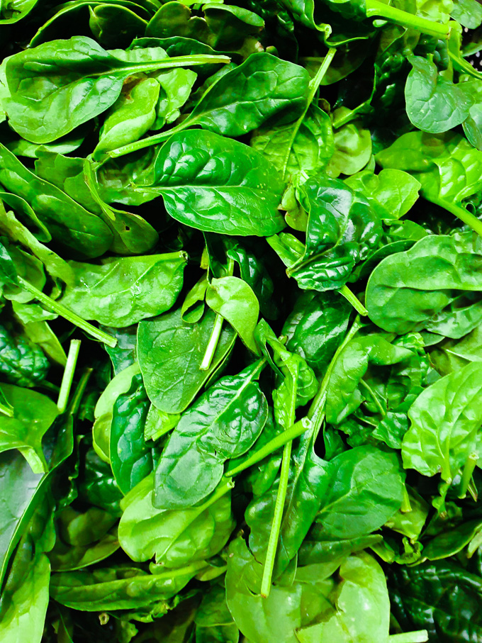Close-up overhead view of fresh spinach leaves.