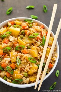 Overhead view of a bowl of Pineapple Fried Rice with chopsticks on the side on a dark background.