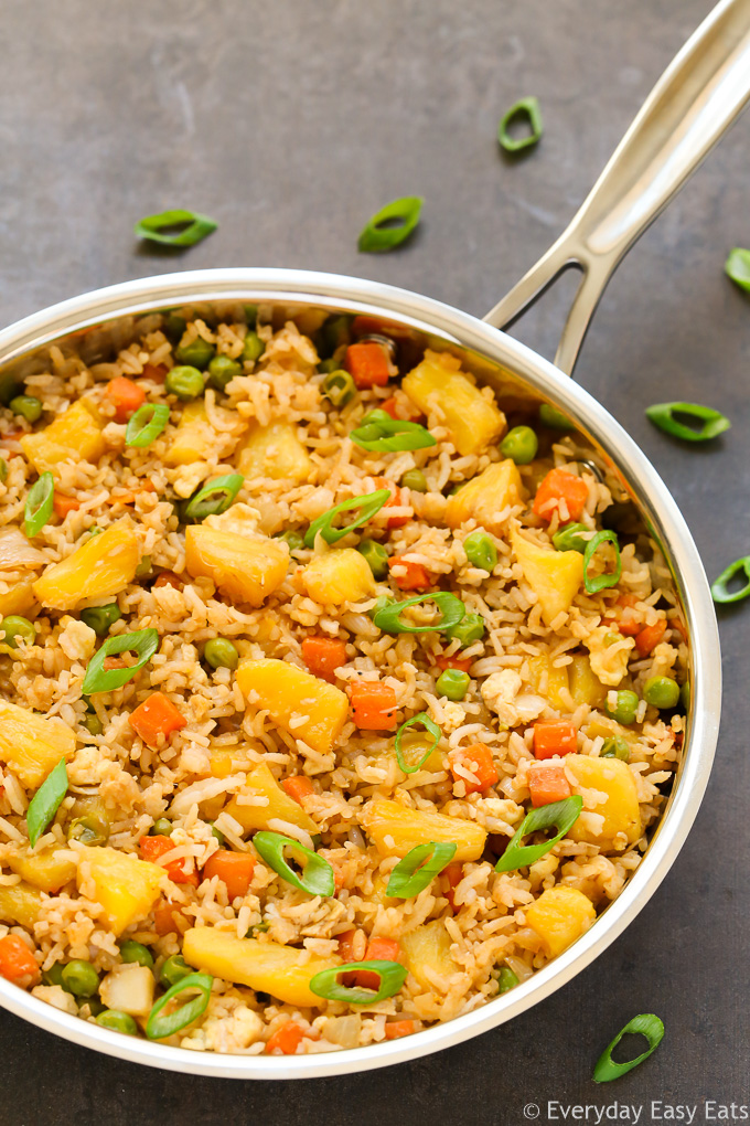Easy Asian Rice Recipes for Dinner: Overhead view of Pineapple Fried Rice in a skillet on a dark background.