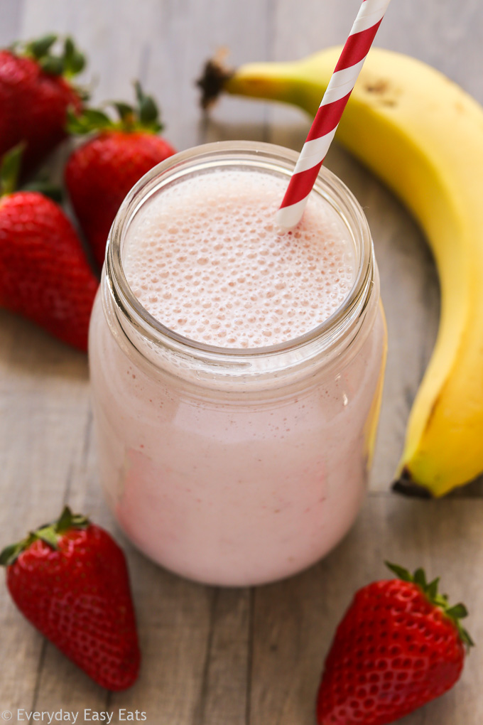 Close-up overhead view of a Strawberry Protein Shake in a glass jar with a straw on a wooden background.