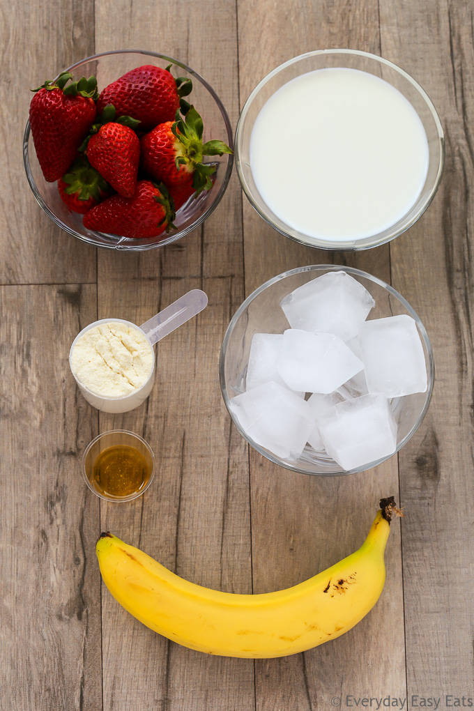 Overhead view of ingredients required to make Strawberry Protein Shake on a wooden background.