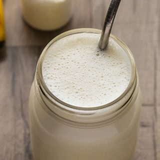 Close-up overhead view of a Vanilla Protein Shake in a glass jar with a metal straw on a wooden background.