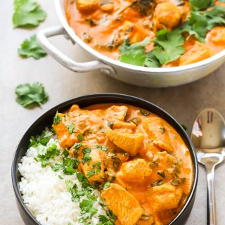 Overhead view of Indian Coconut Chicken Curry with white rice in a bowl with a spoon on the side.