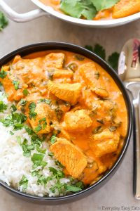 Close-up overhead view of Indian Coconut Chicken Curry with white rice in a bowl with a spoon on the side.