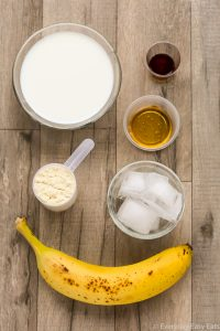 Overhead view of ingredients required to make Vanilla Protein Shake on a wooden background.