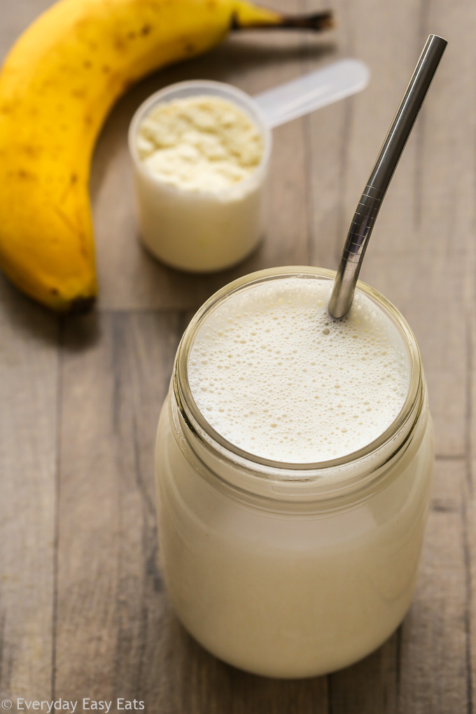 Overhead view of a Whey Protein Shake in a glass mason jar with a metal straw inserted on a wooden background.