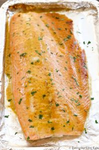Overhead view of Baked Honey Mustard Salmon on a foil-lined baking sheet after being baked in the oven.