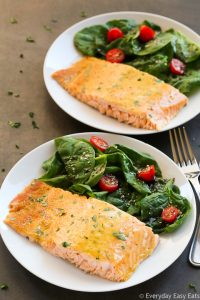Side overhead view of two pieces of Healthy Baked Honey Mustard Salmon in white plates with salad on the side.