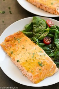 Close-up overhead view of a piece of Healthy Baked Honey Mustard Salmon in a white plate with salad on the side.