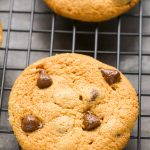 Close-up overhead view of a Flourless Peanut Butter Chocolate Chip Cookie on wire cooling rack.