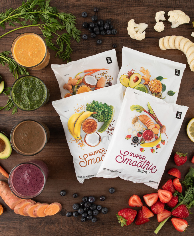 Overhead view of SmoothieBox smoothie packs, blended shakes in glasses and fruit on a wooden background.