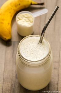 Overhead view of a Vegan Protein Shake in a glass jar with a metal straw on a wooden background.