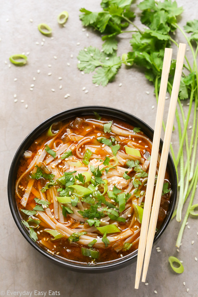 Overhead view of Asian Spicy Noodle Soup in a black bowl with chopsticks on a neutral background.