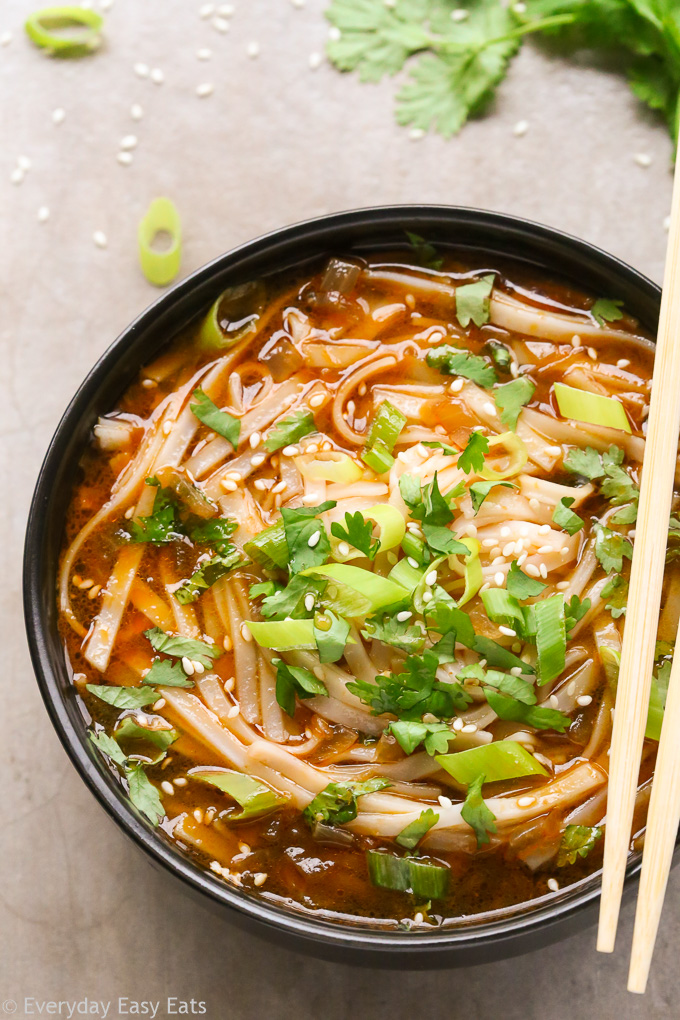Close-up overhead view of Asian Spicy Noodle Soup in a black bowl with chopsticks on a neutral background.