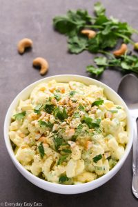 Overhead view of Curried Egg Salad in a white bowl on a black surface.
