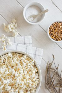 Overhead view of a bowl of popcorn on a white surface