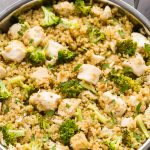 Close-up overhead view of Chicken Broccoli Quinoa in a silver skillet on a black surface.
