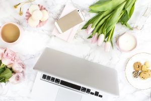 Overhead view of a silver laptop, cell phone, cup of coffee and fresh flowers on a desk.