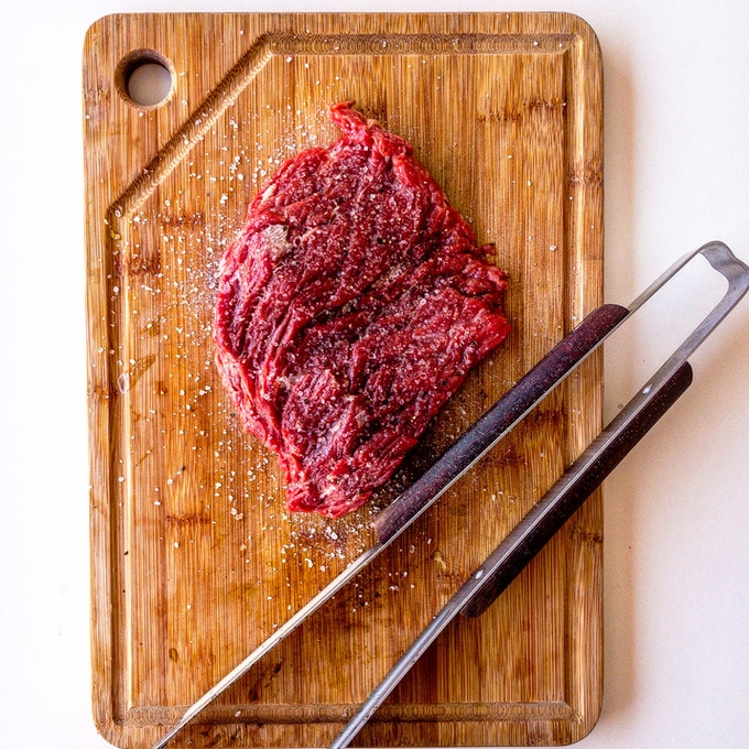 Is It Safe to Order Meat Online: Overhead view of a piece of meat on a wooden chopping board.